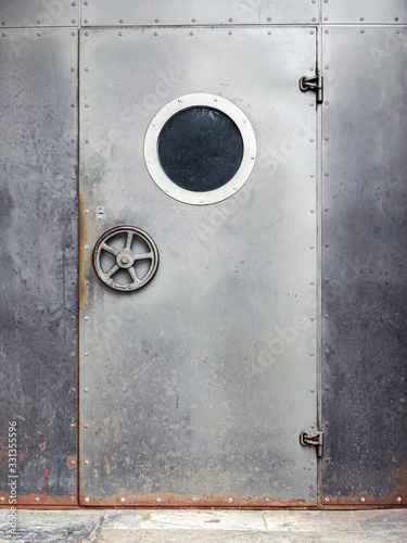 door with porthole. metal door with a round window on rusty metal wall background