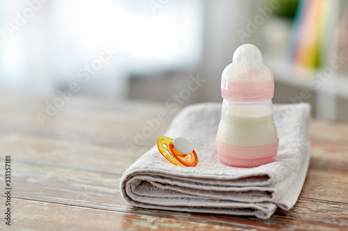 babyhood concept - bottle with baby milk formula, soother and bath towel on wood Fototapet