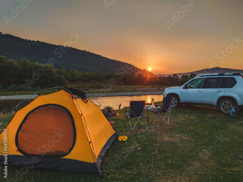 Obraz car travel concept camping place near mountains river - fototapety do salonu