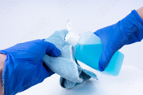 Obraz Putting disinfectant onto a cloth for cleaning - fototapety do salonu