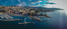 Aerial Drone Panorama Of Morning In Lausanne, Switzerland, With View Froum Ouchy Towards The City. Visible Marina And Whirligig Ladnmark.