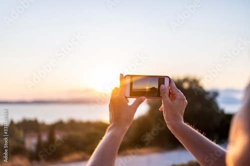 Fototapeta Woman taking a photo with her mobile phone at sunset obraz