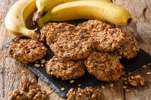 Fotografia Homemade low-calorie banana cookies with oatmeal and walnuts close-up on a slate board
