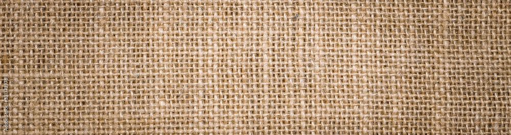 Fototapeta Rough hessian background with flecks of varying colors of beige and brown. with copy space. office desk concept, Hessian sackcloth burlap woven texture background.