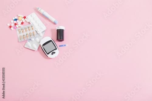 Fototapeta glucometer and pills on  pink background obraz