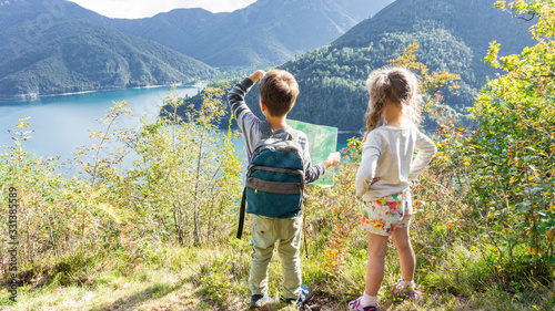 Obraz Two scout children stand on a tourist route along a camping road on the shore of a mountain lake Ledro in the Alps. Kids hiking in the forest in Alps mountains - fototapety do salonu