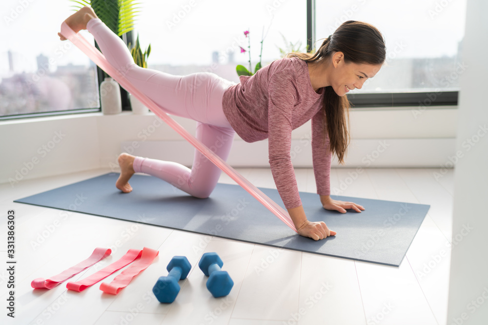 Fototapeta Resistance band fitness at home Asian woman doing leg workout donkey kick floor exercises with strap elastic. Glute muscle activation with kickback for thighs cellulite.
