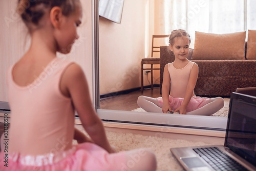 Leinwand Poster Young ballerina practicing classic choreography during online class in ballet sc