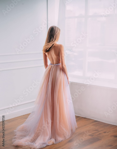 Mysterious young woman princess in elegant beautiful airy luxury long evening trendy dress, bare open back Fototapet