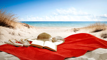 Red Towel On Beach And Book With Summer Hat.