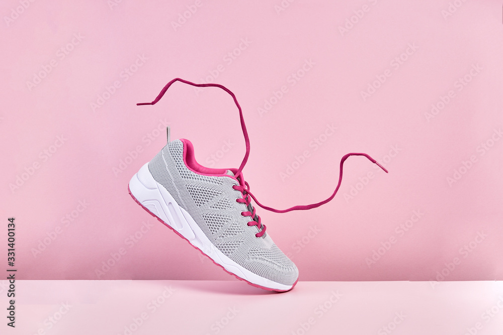Fototapeta Pair of fashion stylish sneakers with flying laces, Running sports shoes on pink background