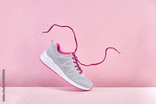 Pair of fashion stylish sneakers with flying laces, Running sports shoes on pink Wallpaper Mural