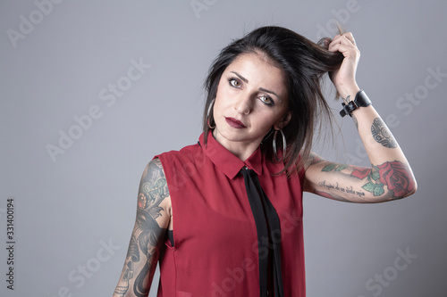 Fotografie, Obraz Ragazza mora con una camicia smanicata rossa e una cravatta nera, piena di tattu