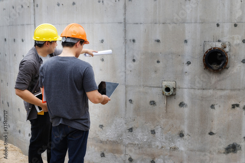 Team of construction workers discussing project details with blueprint in construction site Canvas Print