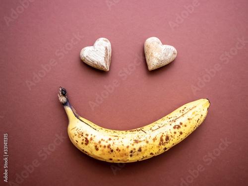 Überreife Banane mit Punkten und zwei Herzen in Gesichtsform, brauner Hintergrun Canvas-taulu