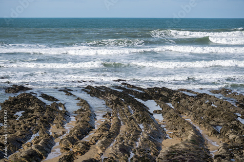 Fotomural rock formations reaching out to the Cornish waves at Widemouth Bay