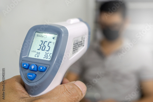 Fotomural Hand holding infrared thermometer to measuring temperature on blurred asia people with face mask on background