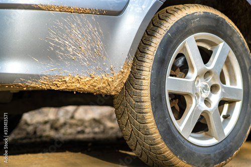 Close up of dirty car wheel with rubber tire covered with yellow mud Slika na platnu