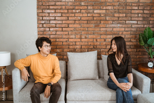 mata magnetyczna couple separating while sitting on a couch. social distancing concept