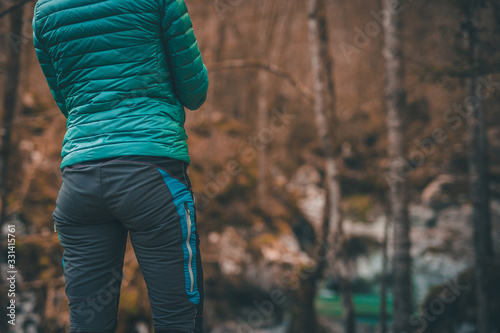 Rear view of a female hiker in modern outdoor clothes posing in front of a magnificent nature scenery with waterfall and trees Canvas Print