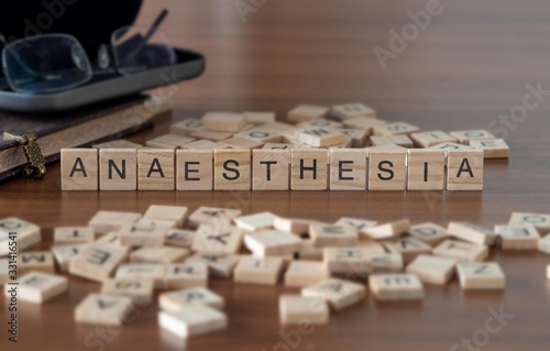 Photo anaesthesia concept represented by wooden letter tiles on a wooden table with gl