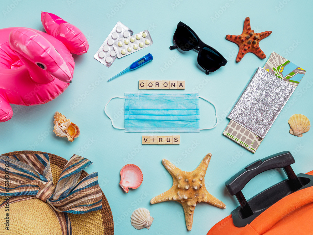 Fototapeta Coronavirus covid-19 and travel concept. Summer vacation and beach rest symbols and breathing mask with wood letters coronavirus on blue background. Flat lay or top view.