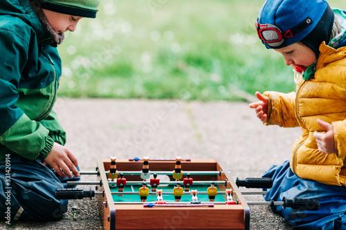 Leinwand Poster Jungen spielen mit Kicker draußen 5