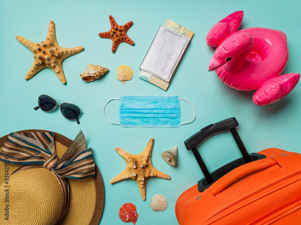 Fototapeta Coronavirus covid-19 and travel concept. Summer vacation and beach rest symbols and breathing mask on blue background. Flat lay or top view.
