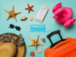 Coronavirus covid-19 and travel concept. Summer vacation and beach rest symbols and breathing mask on blue background. Flat lay or top view.
