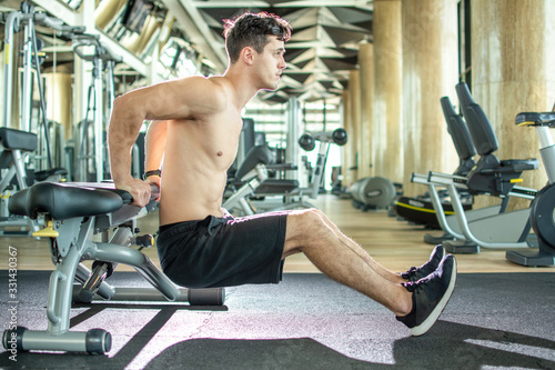 Fototapeta Handsome young shirtless guy doing bench dips exercises at gym