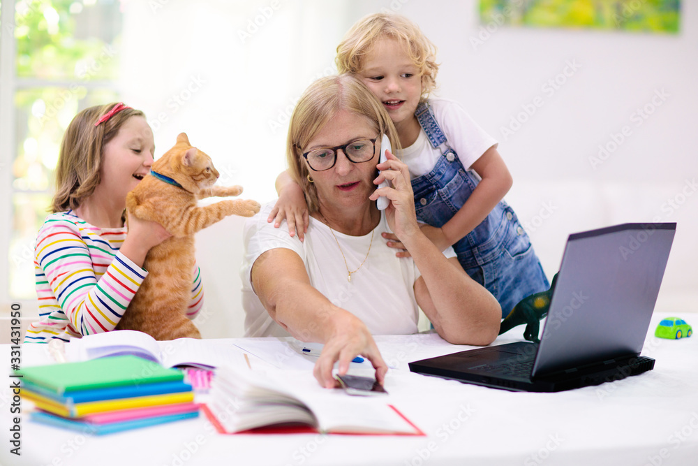 Fototapeta Mother working from home with kids. Quarantine.