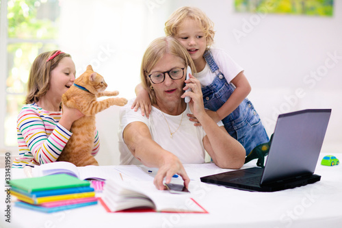 Obraz Mother working from home with kids. Quarantine. - fototapety do salonu
