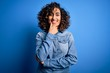 Leinwandbild Motiv Young beautiful curly arab woman wearing casual denim shirt standing over blue background looking confident at the camera smiling with crossed arms and hand raised on chin. Thinking positive.