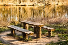 Wooden Table And Benches Surrounded By Greenery And A Lake Under The Sunlight At Daytime