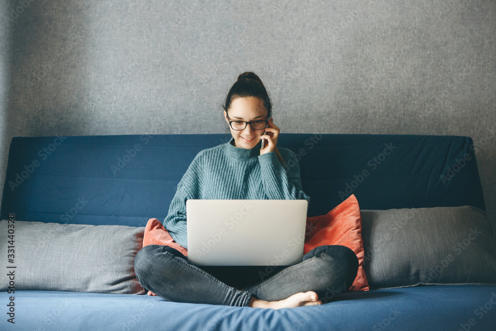 Fototapeta A girl works from home or a student is studying from home or a freelancer. She uses a laptop and a phone.