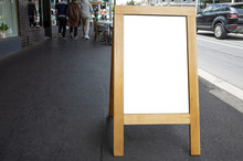 Blank White Outdoor Advertising Stand/sandwich Board Mock Up Template. Clear Street Signage Board With Wooden Frame Placed On Pedestrian Sidewalk. Background Texture Of Standee On Street.