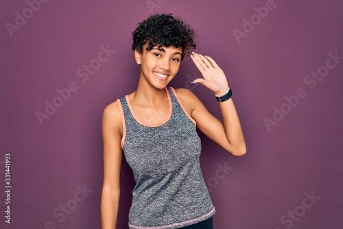 Fototapeta Young beautiful african american afro sportswoman doing exercise wearing sportsw