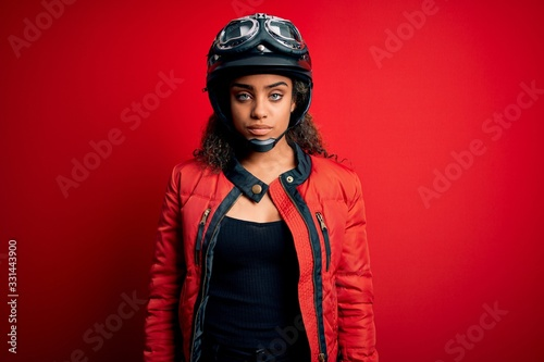 Valokuva Young african american motorcyclist girl wearing moto helmet and glasses over red background with serious expression on face
