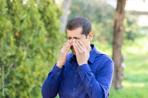 Fotografering Disgusted man rubbing his eyes in a park