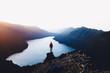 Person auf Felskante mit See im Hintergrund sowie buntem Snnnenaufgang und Lichtstrahlen über Bergketten.
