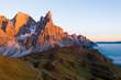 Sonnenuntergang in Dolomiten mit Alpenglühen auf Bergmassiv und kurviger Straße im Vordergrund sowie Blick in nebeliges Tal.