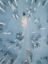 Auto Mit Eingeschaltetem Licht Auf Verschneiter Straße Aus Der Luft Umrundet Von Verschneiten Bäumen Am Polarkreis Zur Blauen Stunde