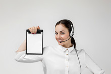 Beautiful Smiling Woman Consultant Of Call Center In Headphones Holding Clipboard With Blank White Paper Sheet On Gray Background. Female Customer Support Operator With Headset