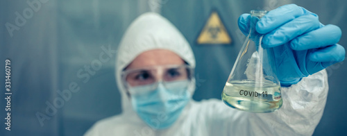 Fotografie, Obraz Female scientist with bacteriological protection suit looking test tube in the laboratory