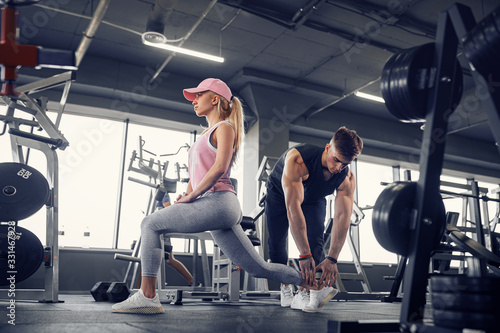 Fototapeta Side view of focused and motivated sporty young blonde girl in sportswear doing legs exercises while handsome muscular personal trainer monitoring her in the gym. obraz