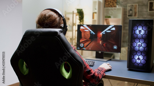 Back view of woman with red hair playing online shooter games Canvas Print