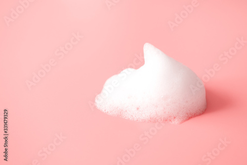 White foam snear from soap, shampoo or cleanser on pink background with selective focus Wallpaper Mural
