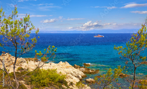 Greece Sithonia Chalkidiki near paradise beach with rock and pine-tree. Scenic landscape Aegean sea and white ship at blue wave.