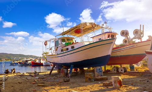 Fishing wooden boats in dock station for repair ships. Greece Sithonia Chalkidiki. Picturesque sunny day with blue sky and white clouds.