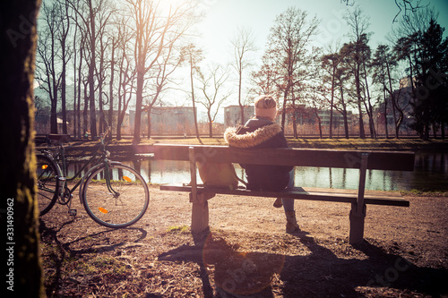 Foto Enjoying the sun in spring: Young girl is sitting on park bench, bicycle back vi